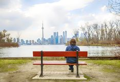 Мальчик подростка сидя на стенде в островах Торонто, Канаде Стоковые Изображения
