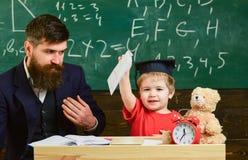 Мальчик показывает его тетрадь с прописями с картинами Оягнитесь счастливые исследования индивидуально с отцом, дома Индивидуальн стоковое изображение