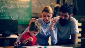 Мальчик показывает его чертежи к родителям в школьном классе учить принципиальной схемы Ребеята школьного возраста в форме Учител сток-видео