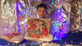 Мальчик показывает подушку рождества, усмехаясь акции видеоматериалы