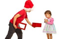 Мальчик показывая к коробке девушки открытой Стоковое Изображение