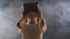 Мальчик получая опыт в использовании VR-шлемофона в закоптелой темной комнате сток-видео