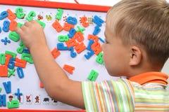 мальчик помечает буквами магнит Стоковое Фото