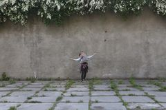 Мальчик поскакал мать против стены серого цвета предпосылки стоковое фото