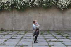 Мальчик поскакал мать против стены серого цвета предпосылки стоковая фотография rf