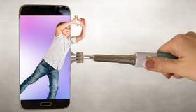 Мальчик посылает сердца через экран телефона Стоковая Фотография