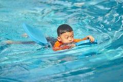 Мальчик практикует поплавать с деструкцией стекловидного тела пусковой площадки пены в воде стоковые фото