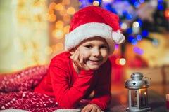 Мальчик представляя в красной шляпе около рождественской елки стоковое фото rf