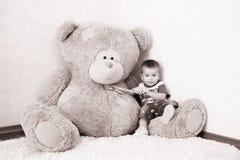 Мальчик представляя около большого плюшевого медвежонка стоковое фото
