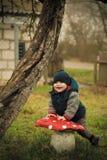 Мальчик представляя около пластинчатого гриба мухы Стоковые Изображения
