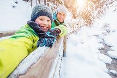 Мальчик принимает фото собственной личности с его отцом на прогулке зимы в горе стоковое фото rf