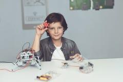 Мальчик приниманся за конструкции робота Он сидит рядом с роботом и показывает робот в камере Стоковые Изображения RF