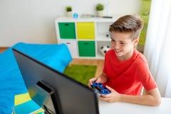 Мальчик при gamepad играя видеоигру на компьютере Стоковое фото RF