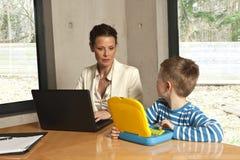 мальчик проверяя мать s компьютера Стоковая Фотография