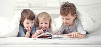 Мальчик 3 прочитал книгу внутри помещения на кровати стоковая фотография rf