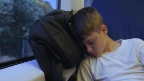 Мальчик путешествует поездом спать около окна на его рюкзаке Сон после путешественника тяжелого дня видеоматериал