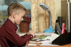 Мальчик работает в его офисе на персональном компьютере Держит ручку Стоковое фото RF