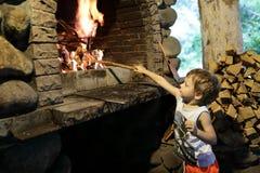 Мальчик разжигает огонь в камине стоковое изображение