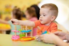 Мальчик ребенка вместе с учителем играя воспитательные игрушки на солнечном дне в питомнике стоковая фотография rf