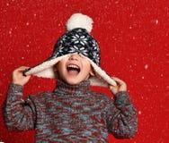 Мальчик ребенка в связанной шляпе и свитере и mittens имея потеху над красочной красной предпосылкой стоковые фотографии rf
