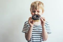 Мальчик ребенка закрыл его глаза и смех с донутом шоколада стоковые фото