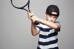 Мальчик ребенка играя теннис Дети спорта стоковая фотография