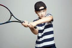 Мальчик ребенка играя теннис Дети спорта стоковые фотографии rf