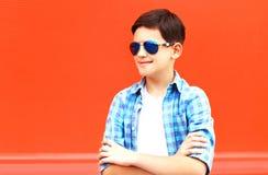 Мальчик ребенка моды портрета в солнечные очки на красочном красном цвете стоковое фото