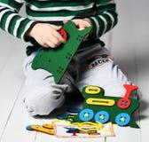 Мальчик ребенк в свете - голубое jshirt с нашивками играет воспитательную игру с деревянными красочными поездом и шнурками стоковая фотография rf