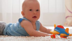 Мальчик ребенк играя с игрушкой дома Милый ребёнок в пижамах вползая на поле и играя с игрушкой сток-видео