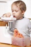 мальчик режа меньшее мясо Стоковая Фотография