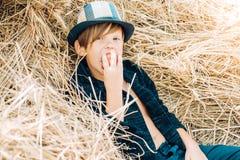Мальчик рекламирует натуральные продучты Счастливый ребенок на осени справедливой Портрет жизнерадостного мальчика лежа в сене сп стоковое изображение
