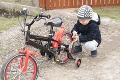 Мальчик ремонтирует велосипед стоковая фотография