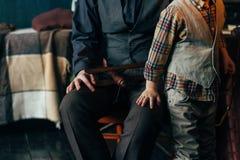 Мальчик рядом с его отцом держит его руку в руке ` s человека самолет игрушки одежды в теплых цветах стоковые фото