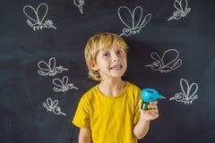 Мальчик сдержан москитами держа fumigator на темной предпосылке На классн классном с покрашенным мелом стоковое фото
