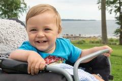 Мальчик сидит в детской дорожной коляске и смеется над Стоковые Фотографии RF