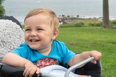Мальчик сидит в детской дорожной коляске и смеется над Стоковое фото RF