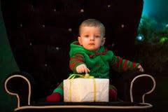 Мальчик сидит в кресле с подарочной коробкой рождества стоковые фото