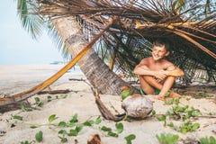 Мальчик сидит в selfmade хате на тропическом пляже и играх в Robi Стоковое Изображение RF