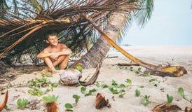 Мальчик сидит в selfmade хате на тропическом пляже и играх в Robi Стоковая Фотография RF