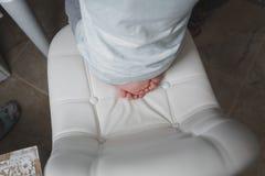 Мальчик сидит на белом стуле Только его пальцы в съемке стоковые изображения rf