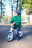 Мальчик сидит на езде велосипеда в парке Стоковое Фото