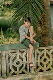 Мальчик сидит на загородке стоковое фото rf