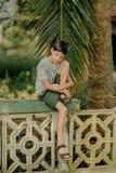 Мальчик сидит на загородке стоковое изображение