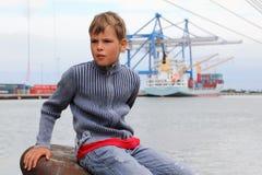 Мальчик сидит на камне на предпосылке корабля Стоковая Фотография