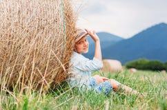 Мальчик сидит на fiild под креном сена - халатном summet в cou Стоковые Изображения