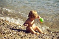 Мальчик сидя в морской воде стоковое изображение