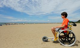 Мальчик сидя на особенной кресло-коляске с колесом алюминиевого сплава стоковое изображение