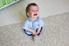 Мальчик сидя на поле, ем осадка ` s и плакать Chil Стоковое Изображение