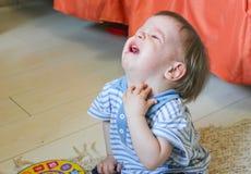 Мальчик сидя на поле, ем осадка ` s и плакать Chil Стоковые Изображения
